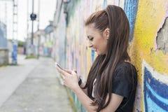 Femme de sourire à l'aide du téléphone dans la rue avec le graffiti Images stock