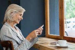 Femme de sourire à l'aide du téléphone intelligent tout en se reposant à la table Image libre de droits