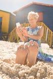 Femme de sourire à l'aide du téléphone intelligent tout en se reposant sur le sable contre des huttes Photographie stock