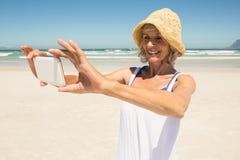 Femme de sourire à l'aide du téléphone intelligent tout en se tenant à la plage Image stock