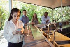 Femme de sourire à l'aide du téléphone portable tout en ayant un verre de champagne Photographie stock libre de droits