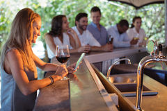 Femme de sourire à l'aide du téléphone portable tout en ayant un verre de vin Images stock
