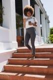 Femme de sourire à l'aide du téléphone portable tout en marchant sur des étapes Image stock
