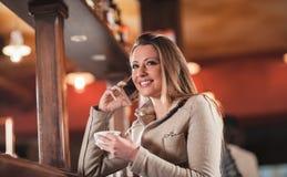 Femme de sourire à la barre ayant un appel téléphonique Photo libre de droits