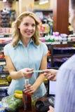 Femme de sourire à la caisse enregistreuse payant avec la carte de crédit Images libres de droits