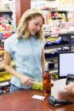 Femme de sourire à la caisse enregistreuse payant avec la carte de crédit Image libre de droits