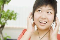 Femme de sourire écoutant des écouteurs image stock
