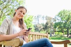 Femme de sourire écrivant un message textuel sur un banc de parc Image libre de droits