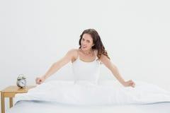 Femme de sourire étirant ses bras dans le lit Image stock