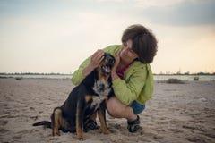 Femme de sourire étreignant avec un chien Photographie stock