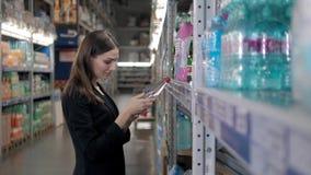 Femme de sourire achetant une bouteille de l'eau dans la section d'épicerie du supermarché, achats de femme d'affaires Photographie stock libre de droits