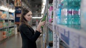 Femme de sourire achetant une bouteille de l'eau dans la section d'épicerie du supermarché, achats de femme d'affaires Photos libres de droits