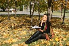 Femme de sourire affichant un livre Photos stock