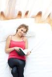 Femme de sourire affichant un livre se trouvant sur son bâti Photographie stock libre de droits