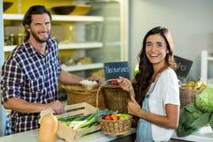 Femme de sourire agissant l'un sur l'autre avec le vendeur tandis que l'achat porte des fruits dans l'épicerie Images stock