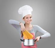Femme de sourire ajoutant les pâtes au pot Images stock