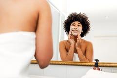 Femme de sourire appliquant la crème naturelle photos libres de droits