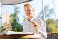 Femme de sourire appréciant la salade en café en plein air Image libre de droits