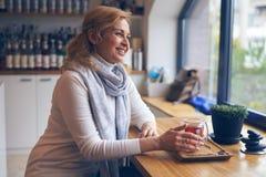 Femme de sourire appréciant la tasse de thé en café Images stock