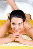 Femme de sourire appréciant un massage arrière à la station thermale Images stock