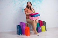 Femme de sourire après l'achat avec des sacs, boîtes, carte d'opérations bancaires, pho Photographie stock libre de droits