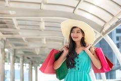 Femme de sourire asiatique de mode de vie ainsi achats heureux dans les vêtements décontractés avec des sacs à provisions photos stock