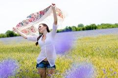 Femme de sourire assez jeune dans le domaine de blé jaune photographie stock libre de droits