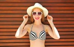 Femme de sourire assez jeune de portrait dans le chapeau d'été de paille Photographie stock