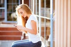Femme de sourire attirante à l'aide du smartphone dehors image stock