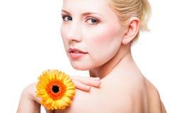 Femme de sourire attirante avec une fleur Image stock