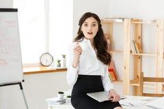 Femme de sourire attirante d'affaires s'asseyant au bureau, tenant une tasse de café, elle est détendante et heureuse images stock