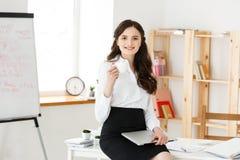 Femme de sourire attirante d'affaires s'asseyant au bureau, tenant une tasse de café, elle est détendante et heureuse images libres de droits