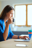 Femme de sourire attirante d'affaires s'asseyant au bureau, tenant une tasse de café Photos stock