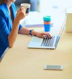 Femme de sourire attirante d'affaires s'asseyant au bureau, tenant une tasse de café Images stock