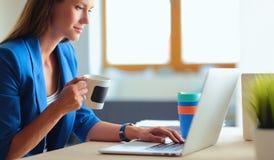Femme de sourire attirante d'affaires s'asseyant au bureau, tenant une tasse de café Photo stock