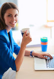 Femme de sourire attirante d'affaires s'asseyant au bureau, tenant une tasse de café Photo libre de droits