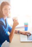 Femme de sourire attirante d'affaires s'asseyant au bureau, tenant une tasse de café Images libres de droits