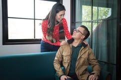 Femme de sourire attirante se tenant avec son mari recherchant affectueusement dans ses yeux Image stock