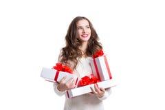 Femme de sourire attirante tenant des boîtiers blancs avec les rubans blancs avec des cadeaux Image libre de droits