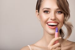 Femme de sourire attirante tenant le rouge à lèvres à disposition photographie stock