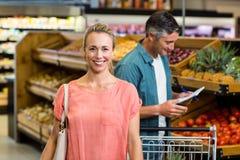 Femme de sourire au supermarché Images stock