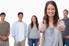 Femme de sourire avec des amis derrière elle renonçant à des pouces Photographie stock libre de droits
