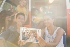 Femme de sourire avec des amis prenant le selfie au terrain de camping Image stock