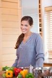 Femme de sourire avec des légumes dans la cuisine photographie stock libre de droits