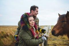 Femme de sourire avec l'homme et le cheval Image stock