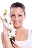 Femme de sourire avec l'orchidée blanche Photographie stock libre de droits