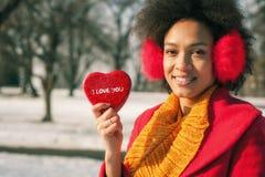 Femme de sourire avec l'oreille chauffant et grand coeur rouge dans le jour d'hiver Photo stock