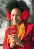 Femme de sourire avec l'oreille chauffant et grand coeur rouge dans le jour d'hiver Images stock