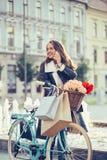 Femme de sourire avec la bicyclette parlant au téléphone portable photographie stock