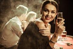 Femme de sourire avec la boisson jouant le tisonnier Image libre de droits